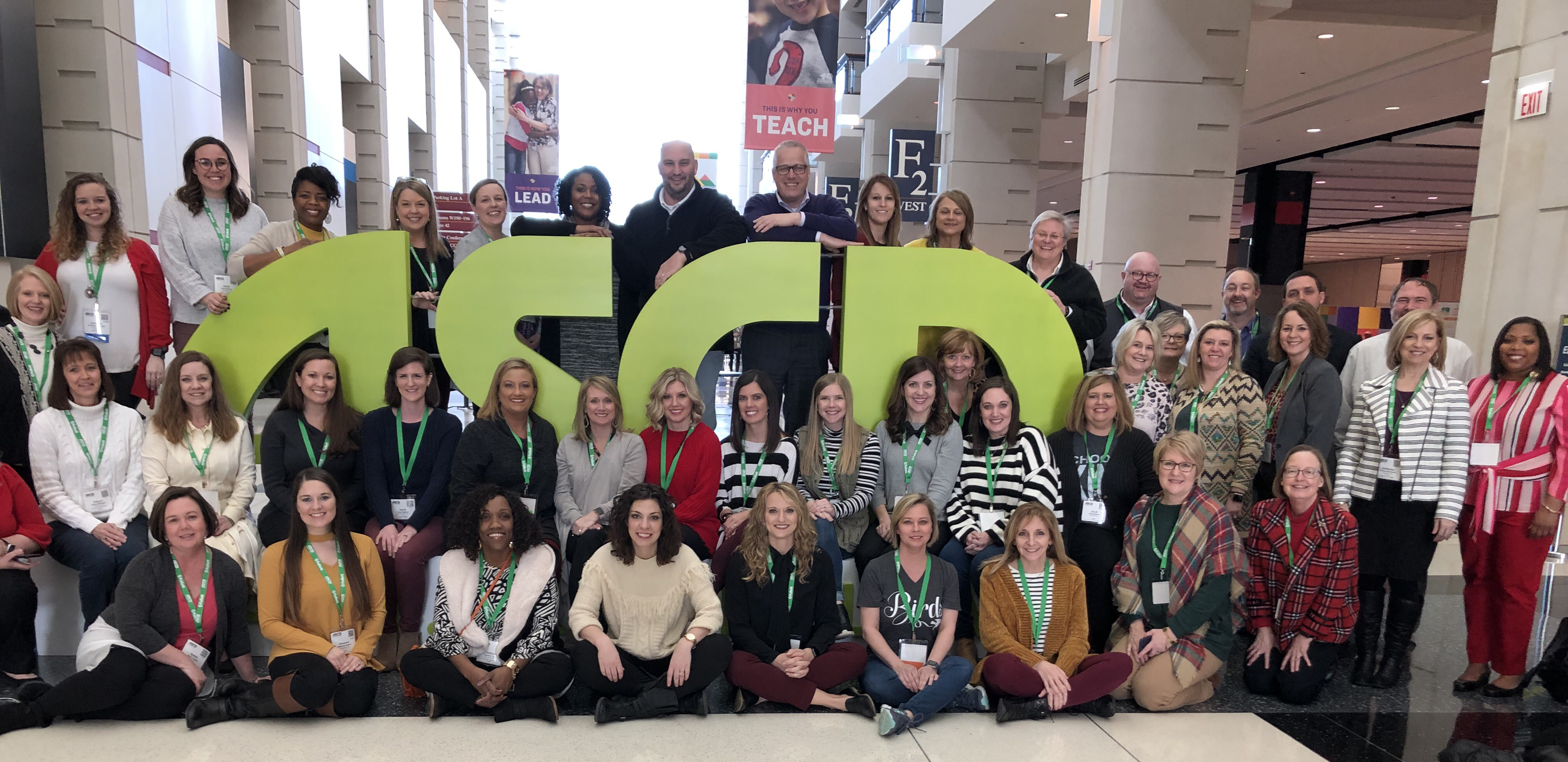 Arkansas ASCD members stand around large versions of the ASCD letters at a conference.